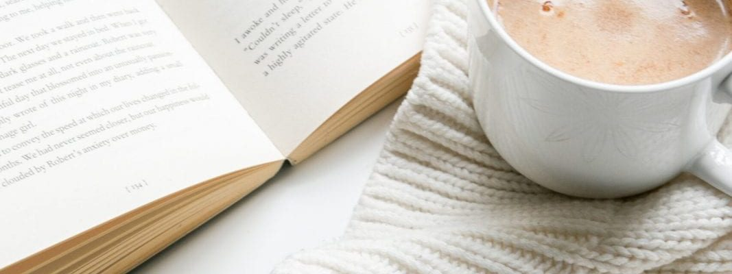 White Blanket with book and cup of Hot Coco